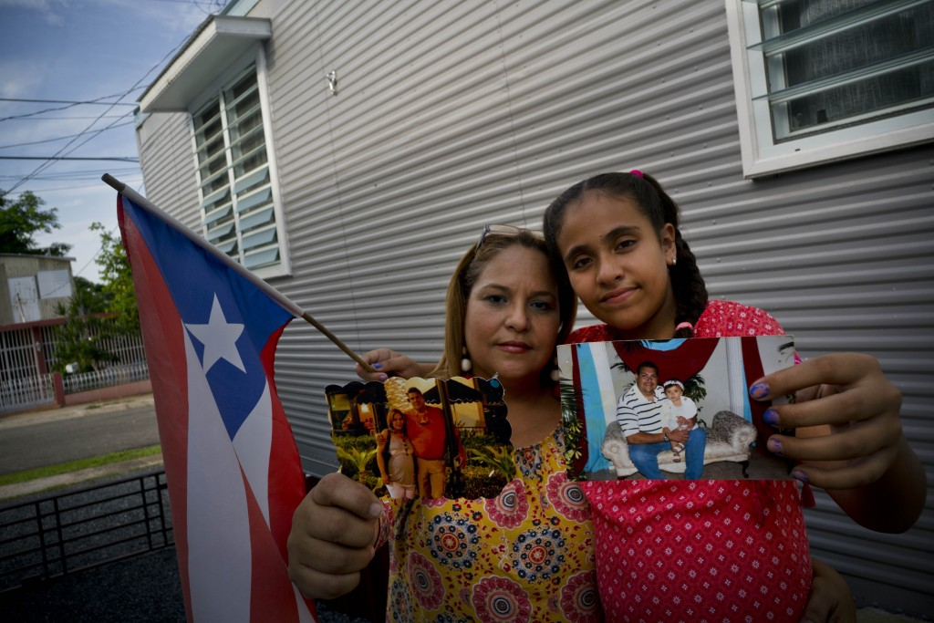 In this Sept. 5, 2018 photo, Lady Diana Torres, left, and her daughter Paula Nicole Lopez, pose with photos of their late husband and father Orlando L