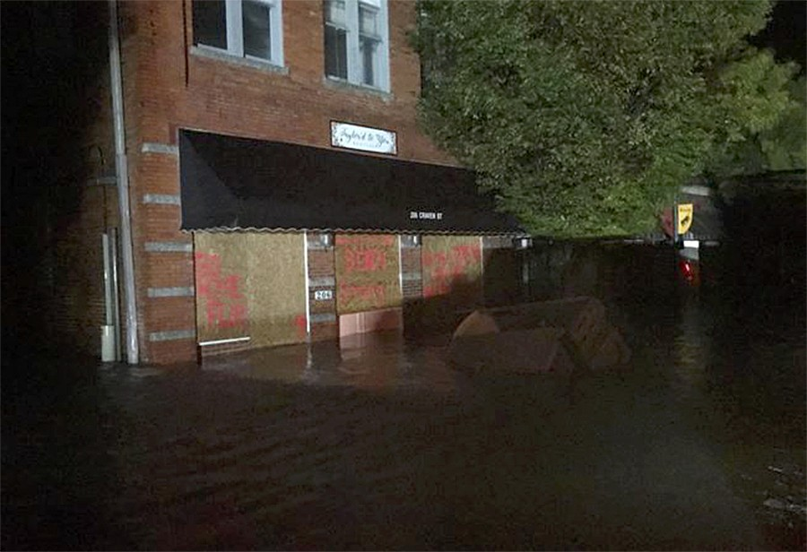 In this photo released by the New Bern Police department, flood waters move near buildings in downtown New Bern, N.C. on Friday, Sept. 14, 2018 as Hur