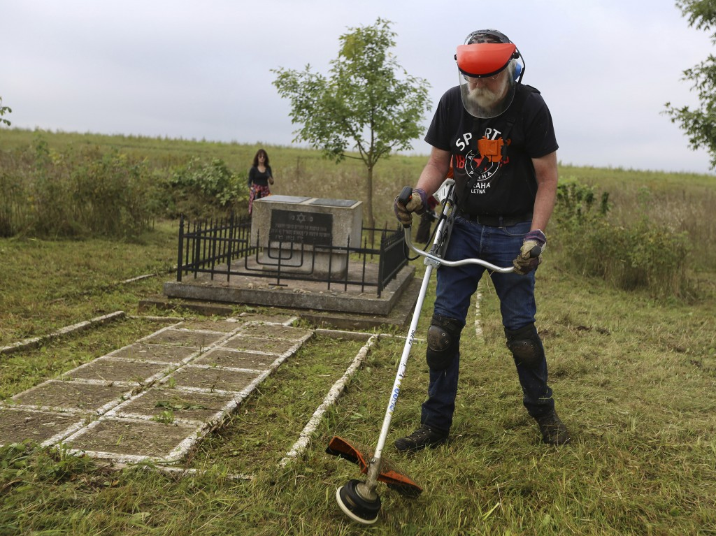 In this photo taken on Aug. 29, 2018, Jay Osborn, a Rohatyn Jewish heritage project leader, cleans an old Jewish cemetery in Rohatyn, the site of a Je...