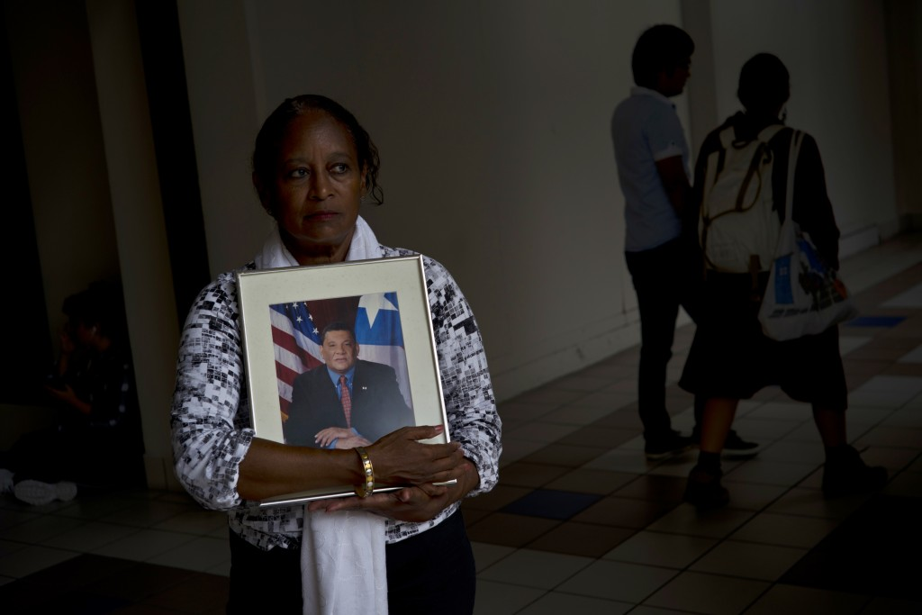 In this Sept. 4, 2018 photo, Gloria Rosado Ortiz poses with an image of her late husband Ernesto Curiel in San Juan, Puerto Rico. Curiel, a 60-year-ol