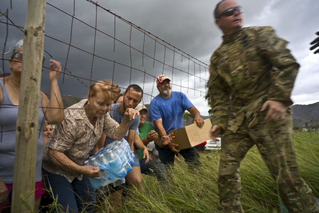 FILE - In this Oct. 7, 2017 file photo, a Puerto Rican National Guard delivers food and water brought by helicopter in the San Lorenzo neighborhood of