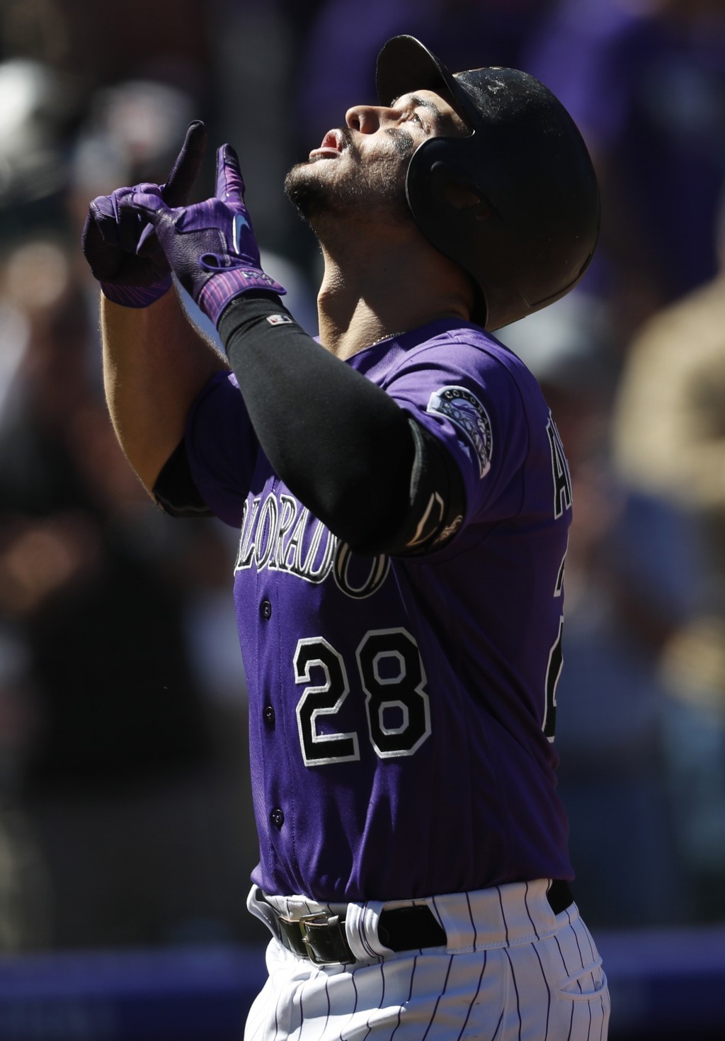 Colorado Rockies' Nolan Arenado gestures as he crosses home plate after hitting a solo home run off Arizona Diamondbacks starting pitcher Matt Koch in