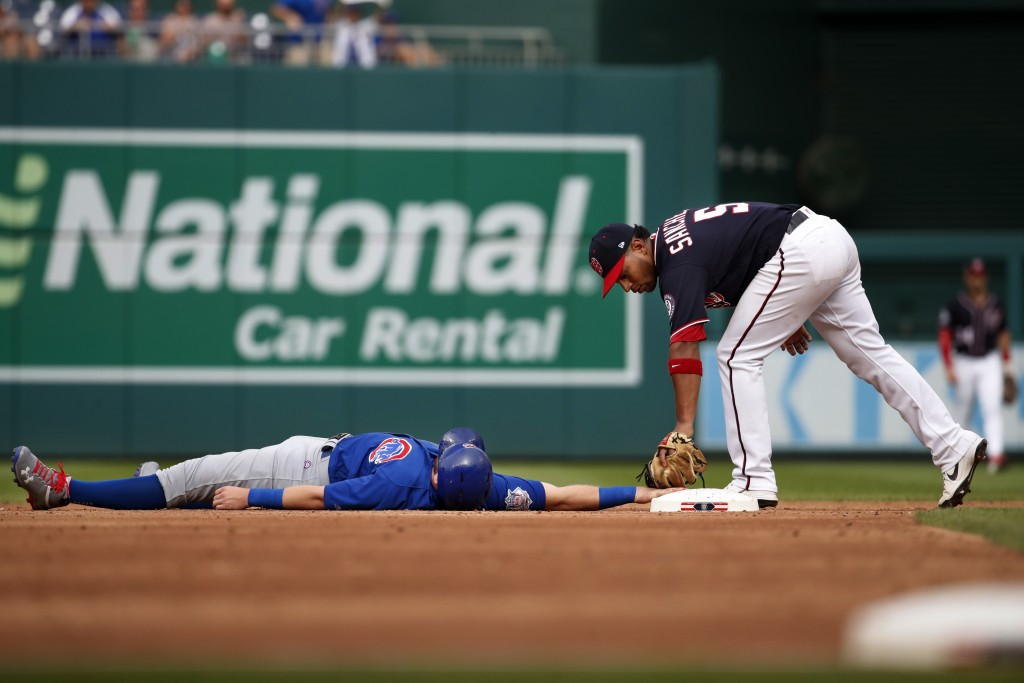 Chicago Cubs' Ian Happ, left, is out at second on being tagged by Washington Nationals second baseman Adrian Sanchez (5) during the third inning of a