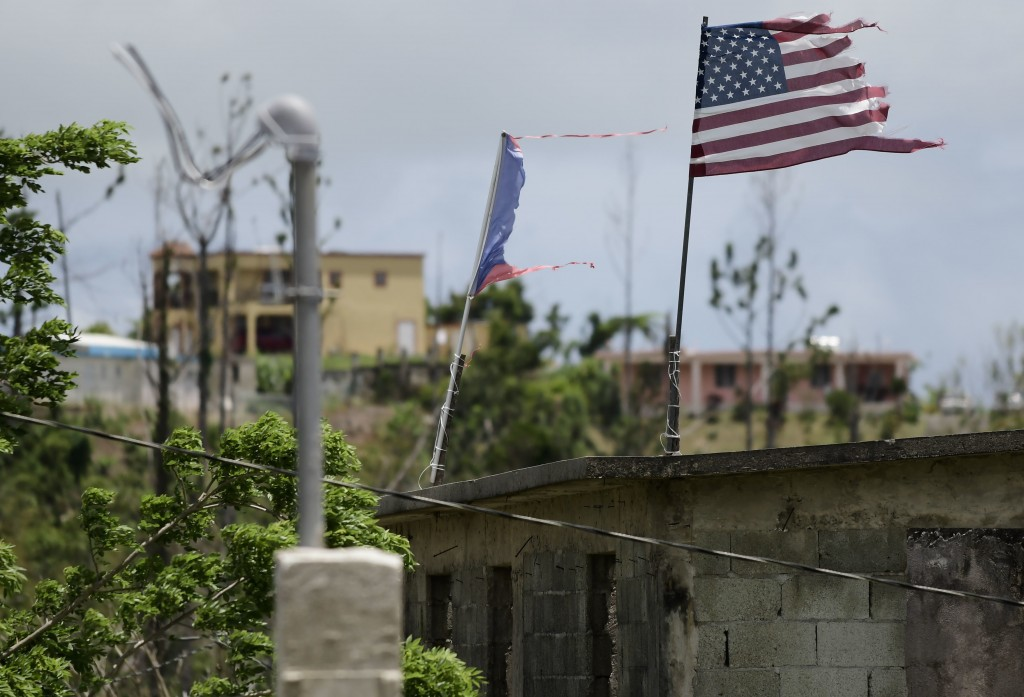 FILE - In this May 16, 2018 file photo, deteriorated U.S. and Puerto Rico flags fly on a roof eight months after the passing of Hurricane Maria in the