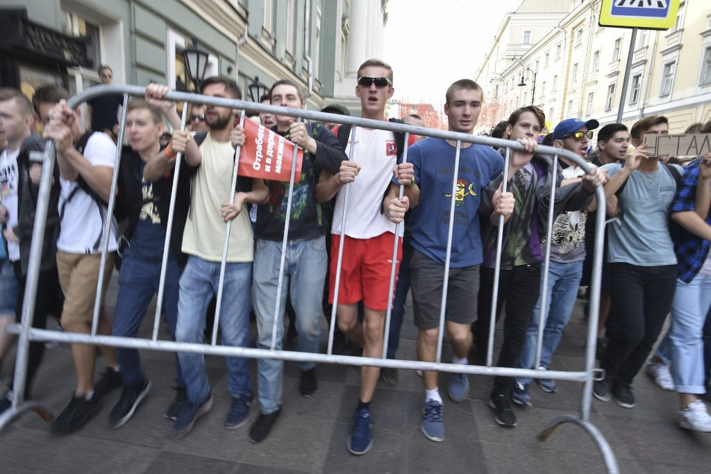 FILE - In this Sunday, Sept. 9, 2018 file photo, young demonstrators carry a police fence during a rally protesting retirement age hikes in Moscow, Ru