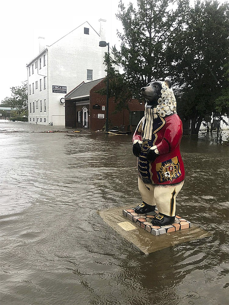 In this photo released by the City of New Bern, N.C., a bear statue floats in flood waters on South Front street in New Bern, N.C. on Friday, Sept. 14