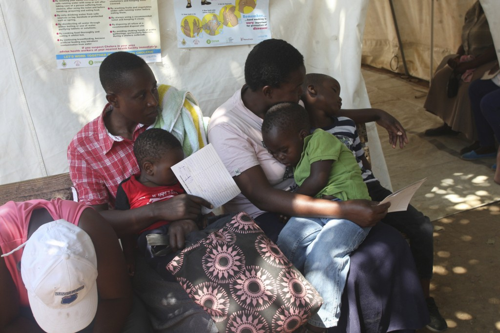 Mothers and their babies suspected to have cholera wait to be screened in a quarantine area in Harare, Friday, Sept, 14, 2018, after a cholera emergen