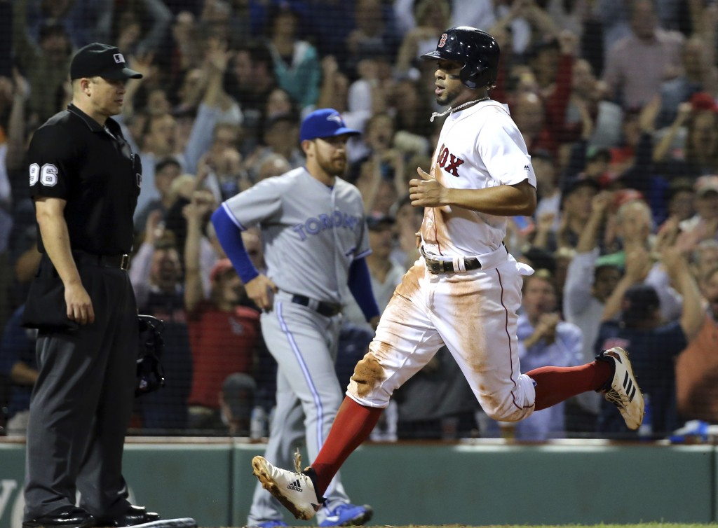 Boston Red Sox's Xander Bogaerts, right, scores from third on an error by Toronto Blue Jays second baseman Yangervis Solarte who mishandled a pop fly