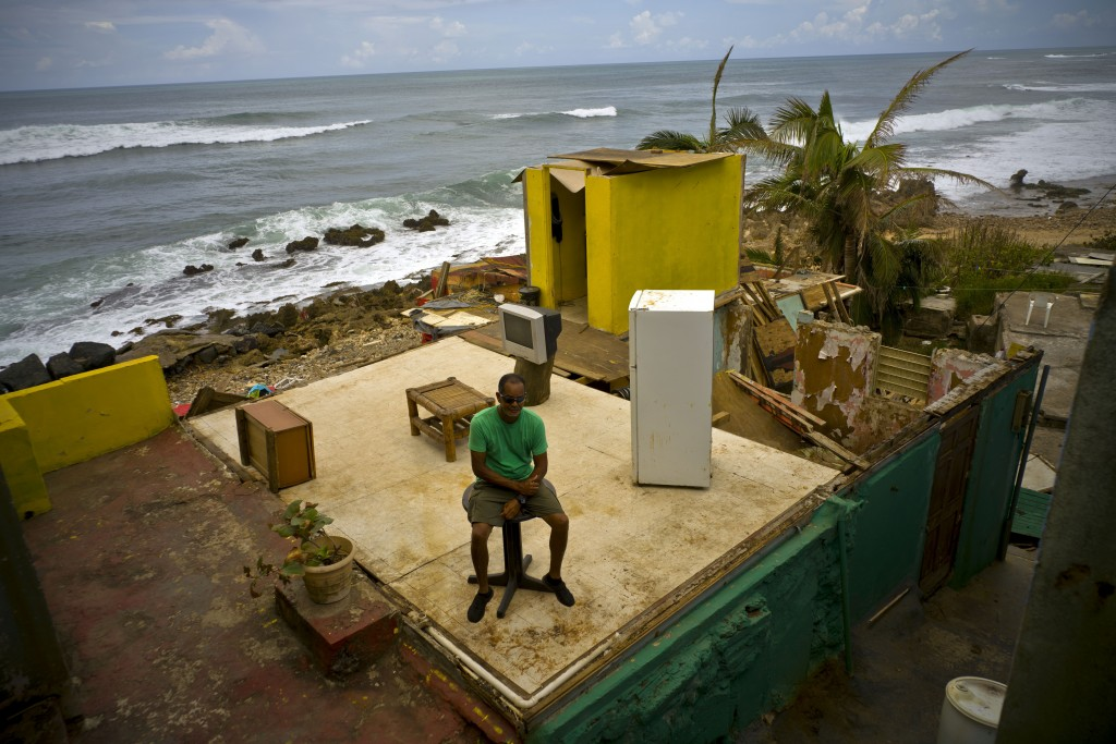 FILE - In this Oct. 5, 2017 file photo, Roberto Figueroa Caballero sits in his home destroyed by Hurricane Maria, two weeks after the storm hit La Per