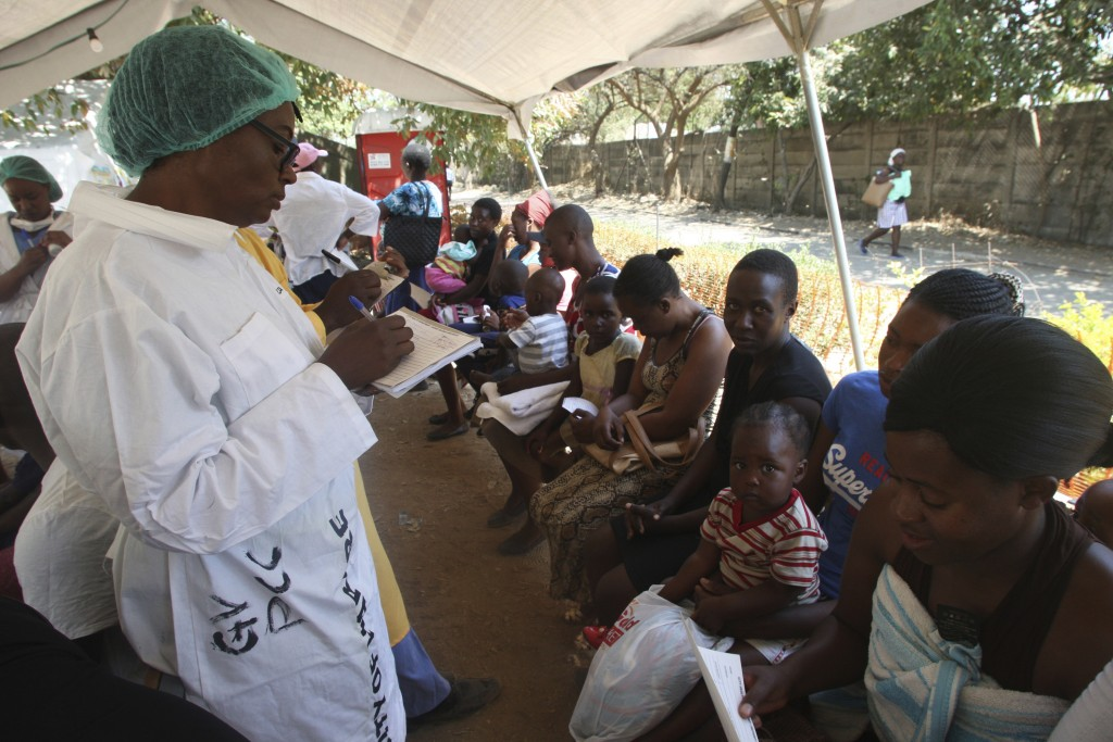A health worker screens mothers and their children for possible symptoms of cholera in a quarantine area in Harare, Friday, Sept, 14, 2018, after a ch