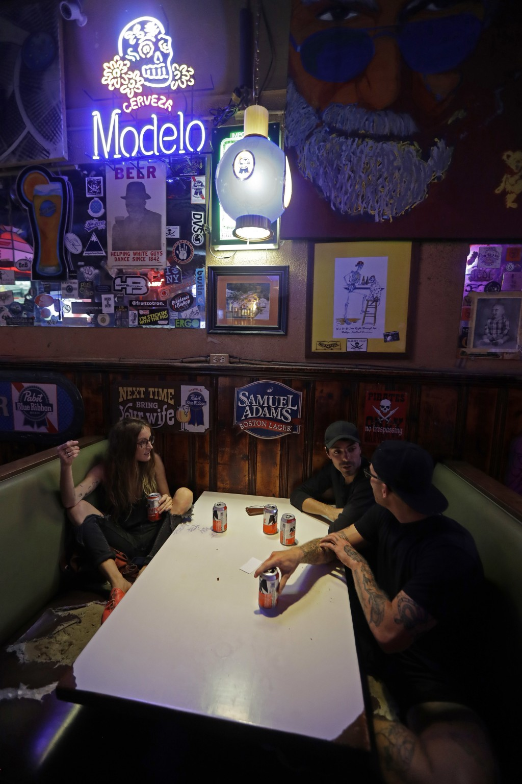Kathryn Cloniger-Kirk, left, Michael Ussery, right, and Steven Harrington, back, chat as they relax at Barbary Coast bar in downtown Wilmington, N.C.,