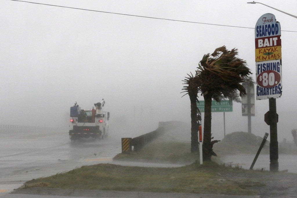 A work truck drives on Hwy 24 as the wind from Hurricane Florence blows palm trees in Swansboro N.C., Thursday, Sept. 13, 2018. (AP Photo/Tom Copeland