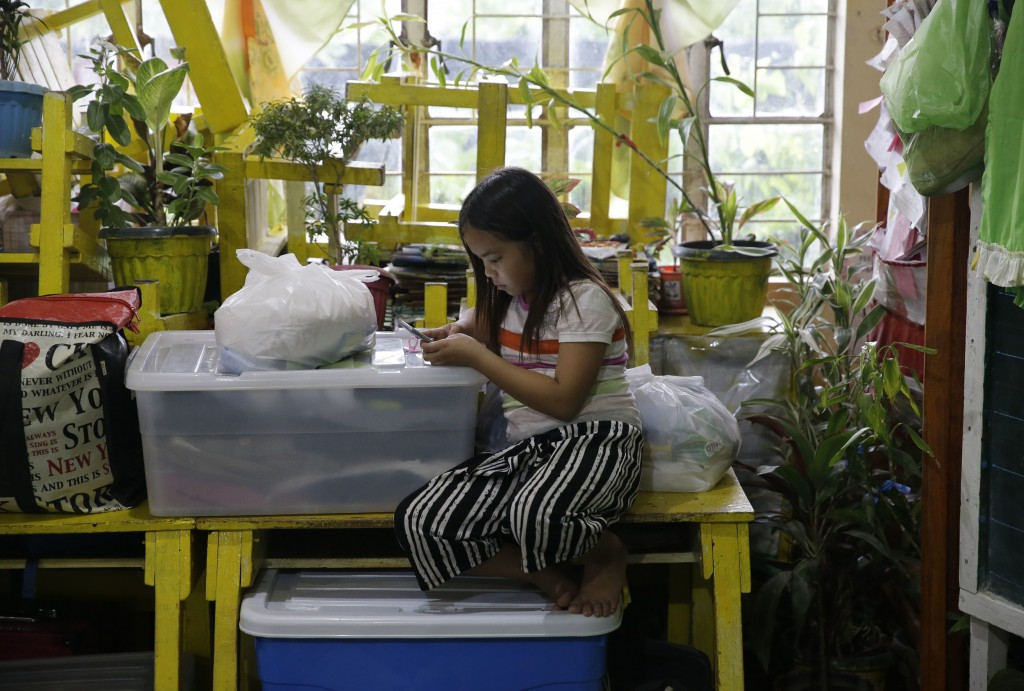A girl uses a smartphone at an evacuation center as rains from Typhoon Mangkhut begin to affect Tuguegarao city, Cagayan province, northeastern Philip
