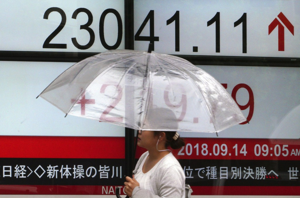 A woman walks past an electronic stock board showing Japan's Nikkei 225 index at a securities firm in Tokyo Friday, Sept. 14, 2018. Asian shares were ...