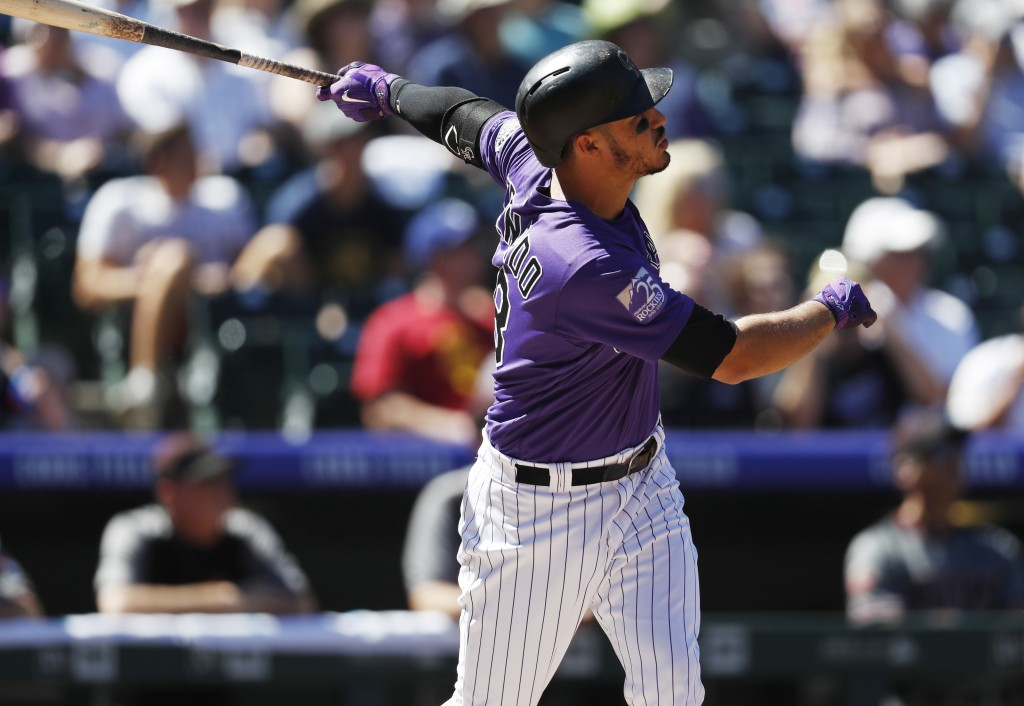 Colorado Rockies' Nolan Arenado follows the flight of his solo home run off Arizona Diamondbacks starting pitcher Matt Koch in the first inning of a b