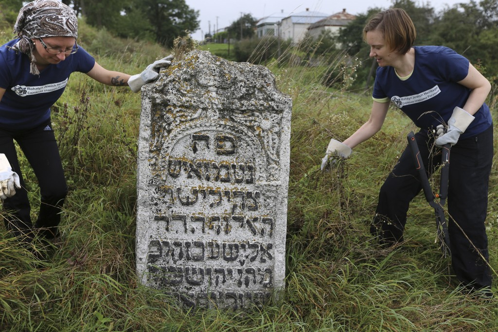 In this photo taken on Aug. 29, 2018, volunteers clean an old Jewish cemetery in Rohatyn, the site of a Jewish Heritage project, close to Lviv, Ukrain...