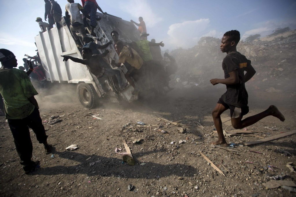 In this Aug. 28, 2018 photo, scavengers climb on a trash truck arriving to unload at the Truitier landfill in the Cite Soleil slum of Port-au-Prince,