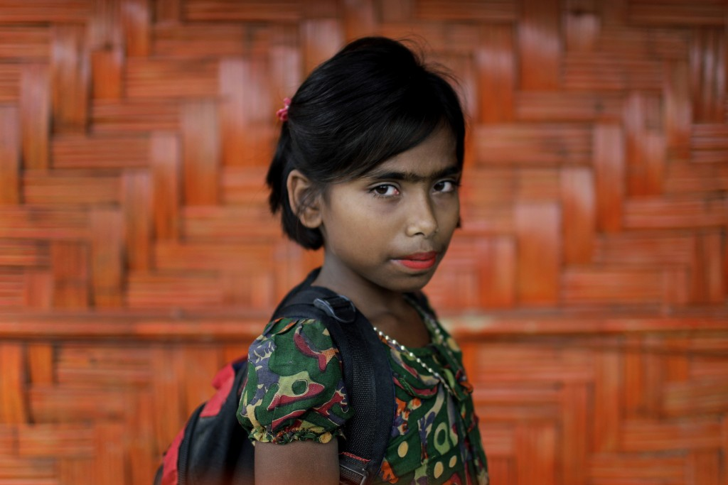 In this June 27, 2018, photo, Taslima, 10, poses for a portrait in front of her classroom in Chakmarkul refugee camp, Bangladesh. Amid the misery and