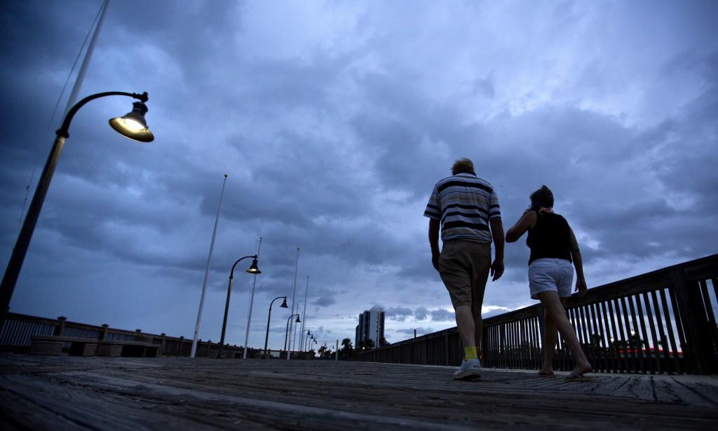 A couple walks along the boardwalk as Hurricane Florence approaches Myrtle Beach, S.C., Thursday, Sept. 13, 2018. (AP Photo/David Goldman)