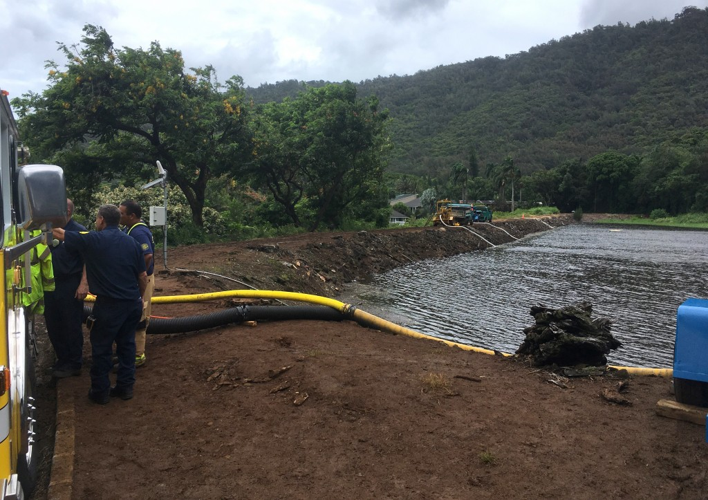 Officials pump water from a reservoir where a dam came close to overflowing in Honolulu on Thursday, Sept. 13, 2018. Honolulu officials say they may n