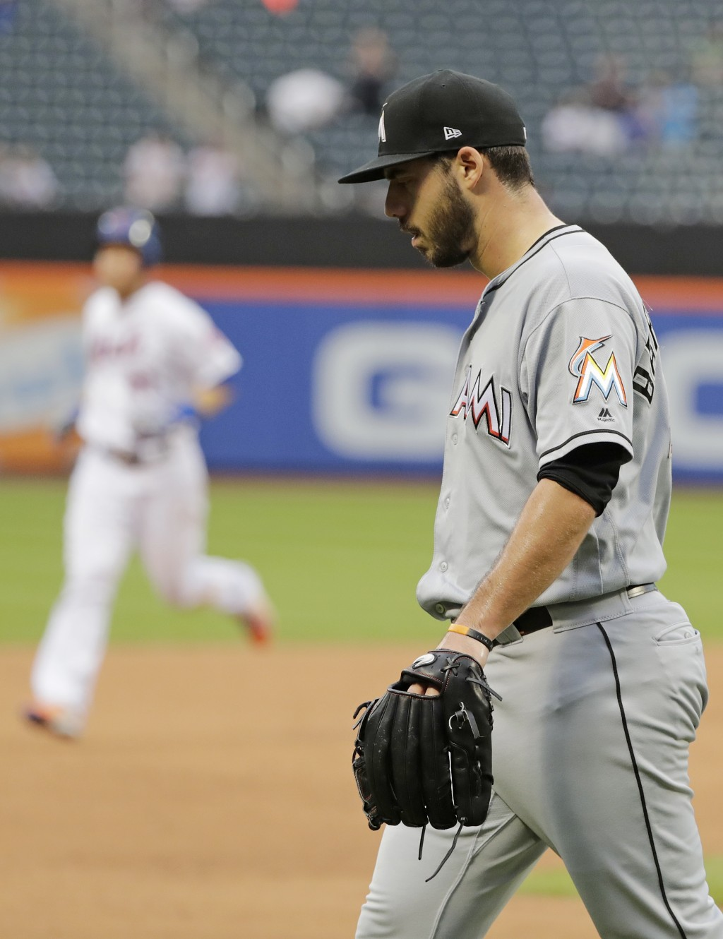 Miami Marlins relief pitcher Kyle Barraclough, right, reacts as New York Mets' Todd Frazier runs the bases after hitting a walkoff home run during the