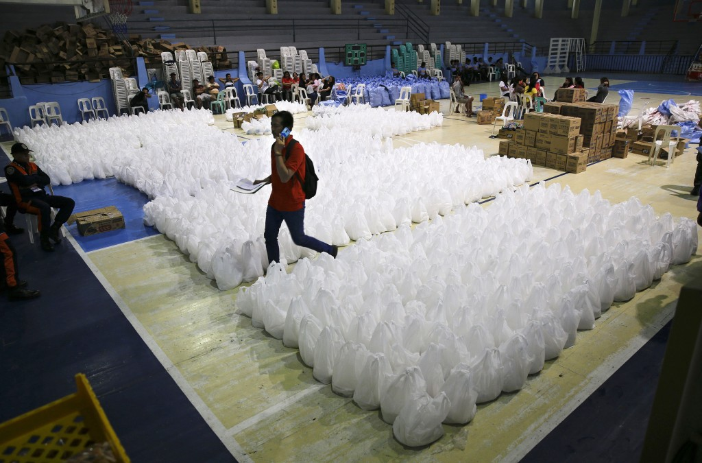 A volunteer passes by packs of relief goods as rains from Typhoon Mangkhut begin to affect Tuguegarao city, Cagayan province, northeastern Philippines...
