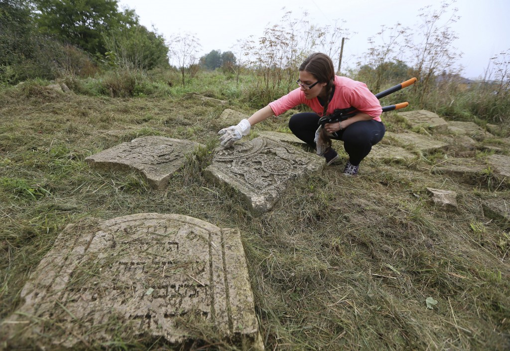 In this photo taken on Aug. 29, 2018, a volunteer cleans an old Jewish cemetery in Rohatyn, the site of a Jewish Heritage project, close to Lviv, Ukra...