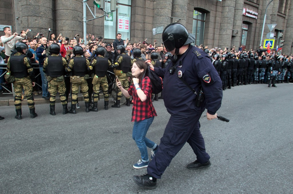 FILE - In this Sunday, Sept. 9, 2018 file photo, a Russian police officer detains a teenager during a rally protesting retirement age hikes in St. Pet