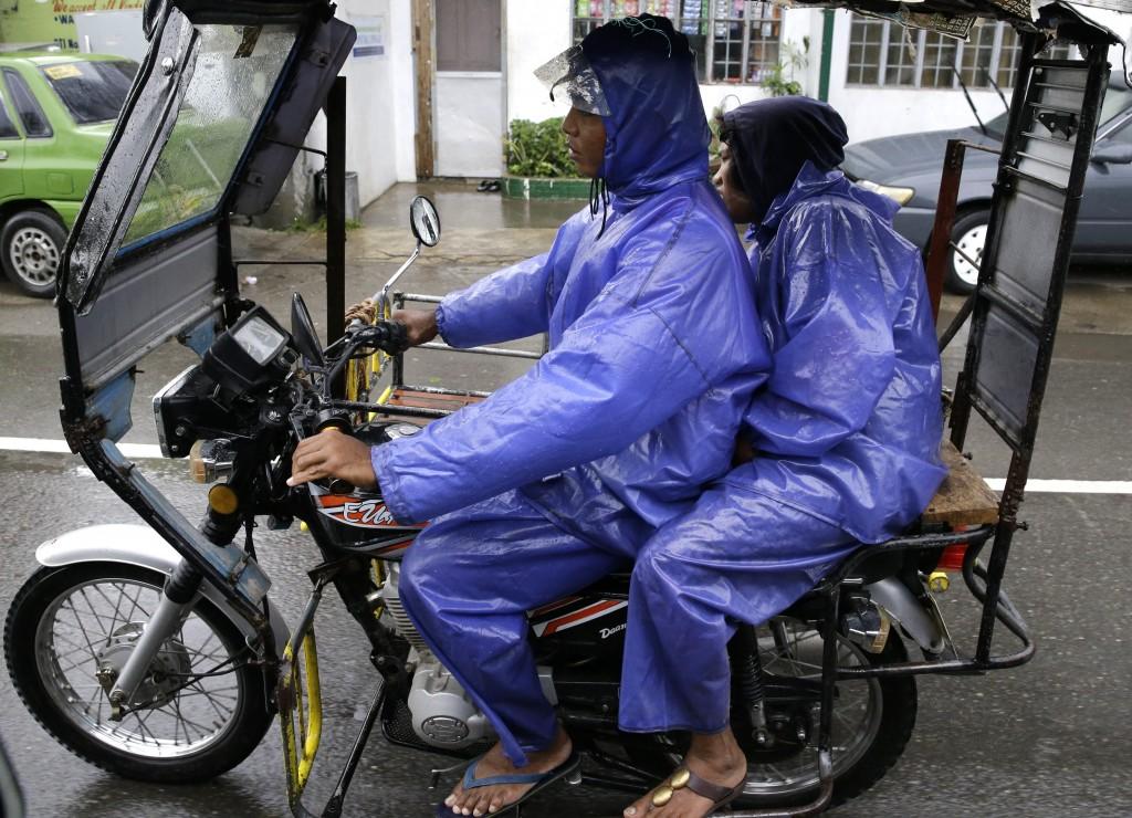 Residents wear raincoats during rain as Typhoon Mangkhut nears Tuguegarao, Cagayan province, northeastern Philippines Friday, Sept. 14, 2018. Typhoon ...