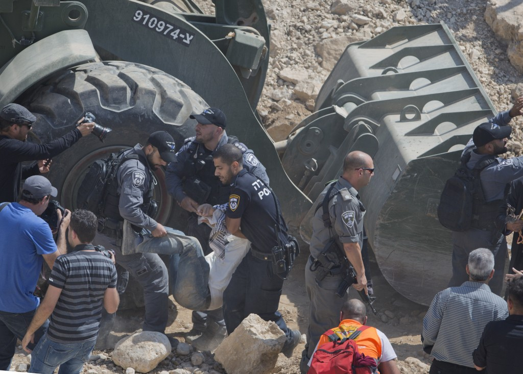 Israeli border police arrest protesters and activists blocking Israeli army bulldozer operating at the West Bank Bedouin community of Khan al-Ahmar, F