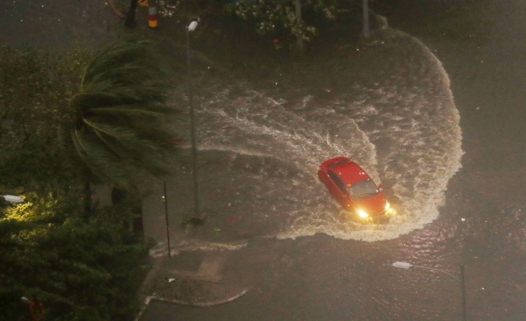 FILE - In this Saturday, Sept. 15, 2018, file photo, a vehicle negotiates a flooded street in Manila as Typhoon Mangkhut continues to batter the north