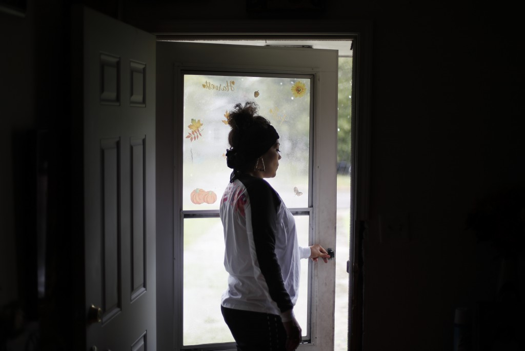 Shewanna Lewis looks out her front door in Lumberton, N.C., Friday, Sept. 14, 2018, while waiting to be evacuated by her sister as Hurricane Florence