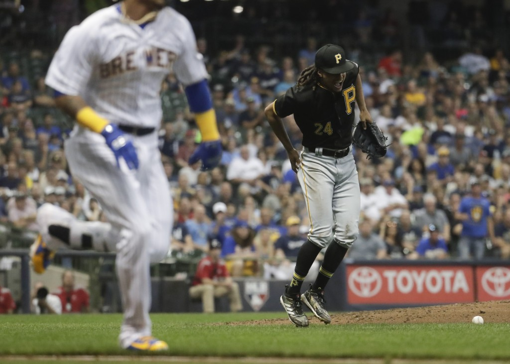 Pittsburgh Pirates' Chris Archer reacts after being hit by a ball hit by Milwaukee Brewers' Orlando Arciaduring the fifth inning of a baseball game Fr