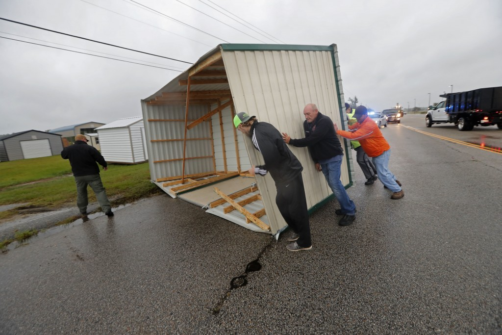 People move a wood and metal structure off a roadway after winds from Hurricane Florence blew it off a sales lot in Florence, S.C., Friday, Sept. 14,
