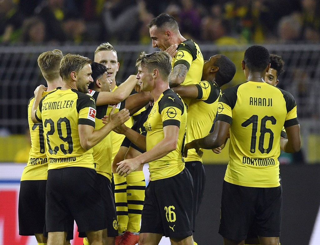 Dortmund's new forward Paco Alcacer, up, is celebrated by teammates after he scored his side's third goal at his debut during the German Bundesliga so