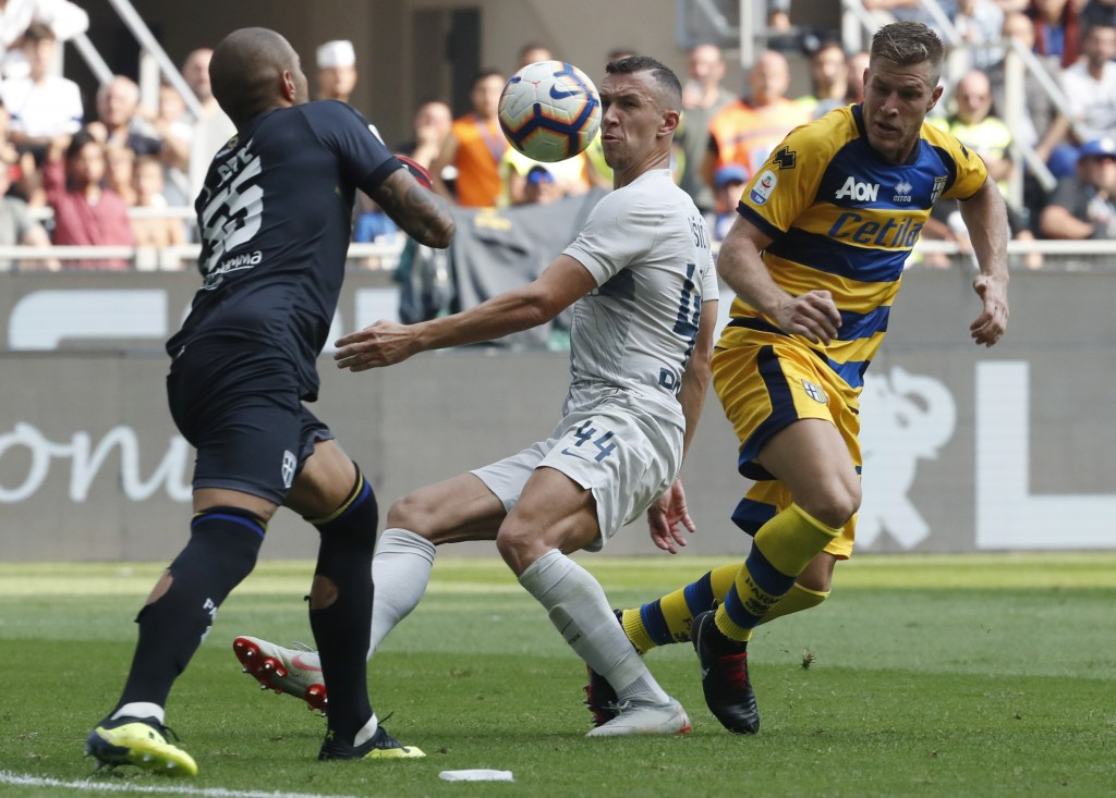 Inter Milan's Ivan Perisic, center, and Parma goalkeeper Luigi Sepe, left, battle for the ball during their Series A Soccer match between Inter Milan