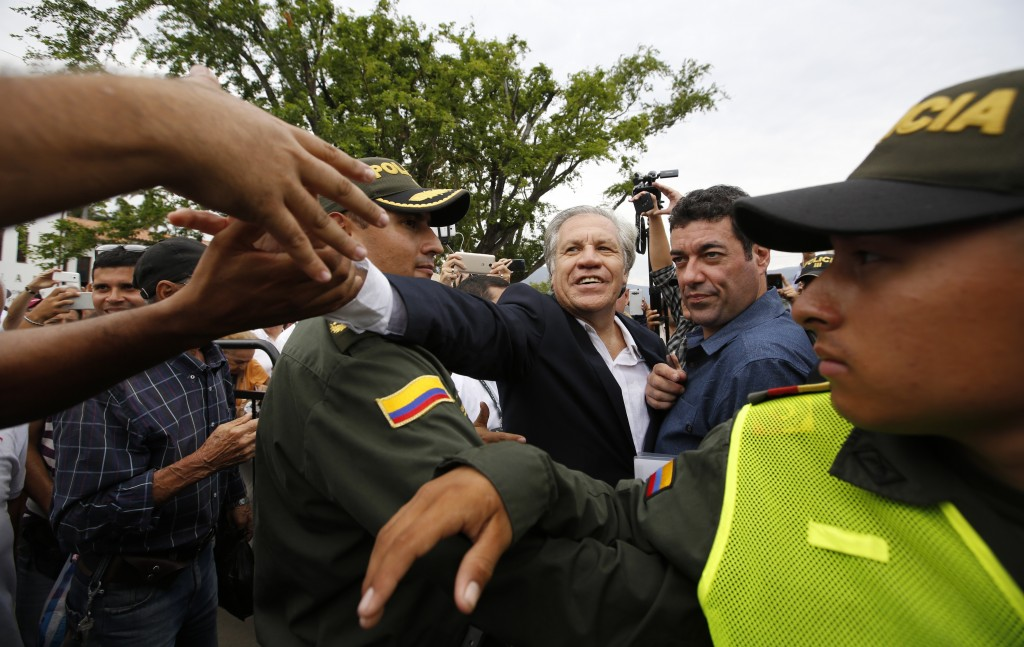 Organization of American States Secretary-General Luis Almagro reaches across a cordon of police to shake hands with a Venezuelan migrant in La Parada