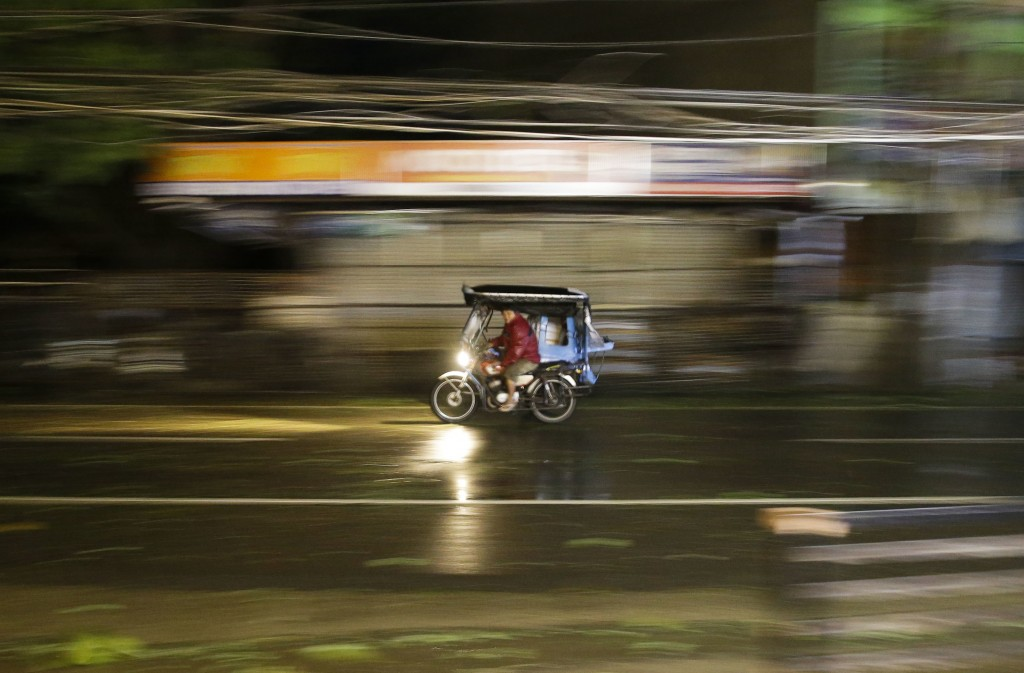 A man rides his tricycle as strong winds and rain from Typhoon Mangkhut batter Tuguegarao city, Cagayan province, northeastern Philippines on Saturday