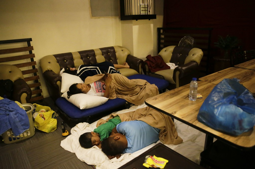 Guests sleep inside a hotel restaurant after the roof of their room was partly damaged due to strong winds from Typhoon Mangkut in Tuguegarao city, Ca