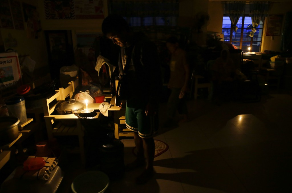 Evacuees use candles inside a temporary evacuation center as electricity was shut-off following the onslaught of Typhoon Mangkhut in Tuguegarao city i...