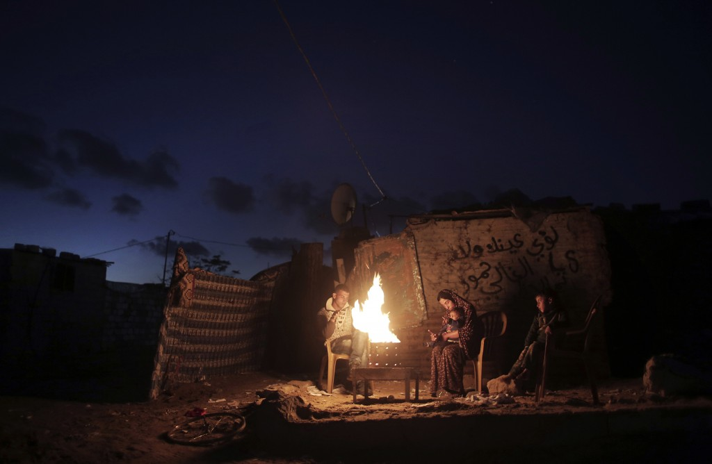 FILE - In this Jan. 15, 2017 file photo, a Palestinian family warm themselves with a fire outside their makeshift house during a power cut in a poor n