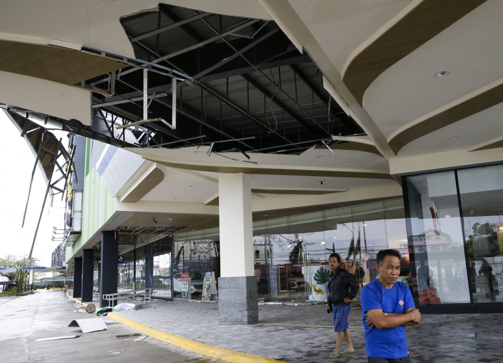 Residents stand beside a damaged portion of a mall due to strong winds from Typhoon Mangkhut as it barreled across Tuguegarao city in Cagayan province