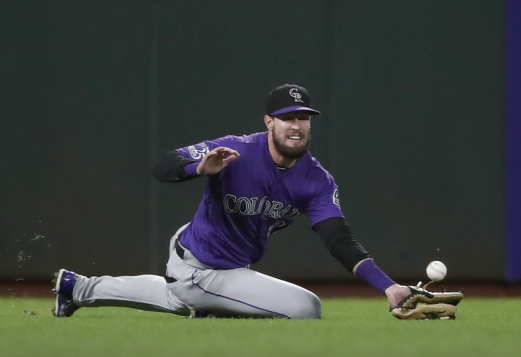 Colorado Rockies left fielder David Dahl cannot make the catch on a fly ball by San Francisco Giants' Joe Panik during the fourth inning of a baseball