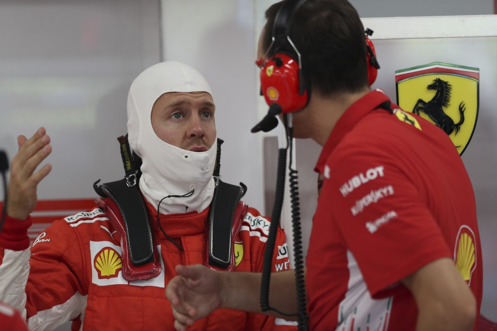 Ferrari driver Sebastian Vettel of Germany, left, talks with team mechanic during first practice at the Marina Bay City Circuit ahead of the Singapore...