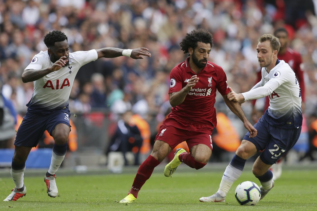 Liverpool's Mohamed Salad, center, vies the ball past Tottenham's Christian Eriksen, right during the English Premier League soccer match between Tott