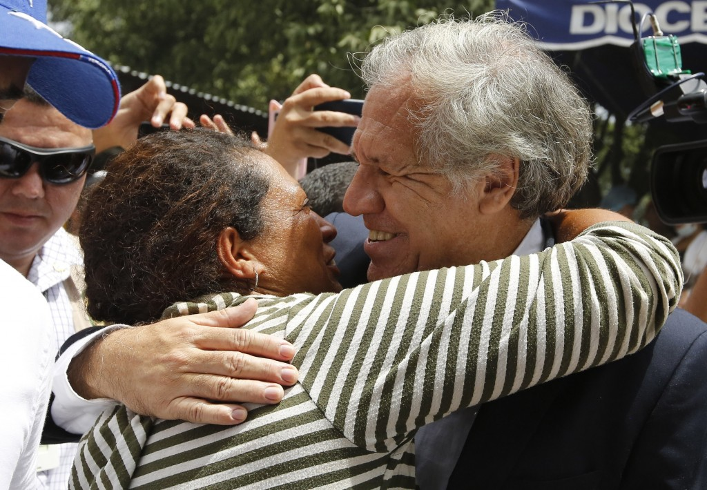 "Organization of American States Secretary-General Luis Almagro, right, embraces a Venezuelan migrant at the ""Divina Providencia"" migrant shelter, in L"