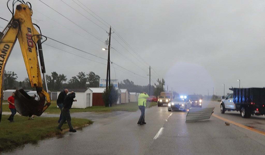 A piece of corrugated metal blown by winds from Hurricane Florence just misses a state patrolman as people move a wood and metal structure that was bl