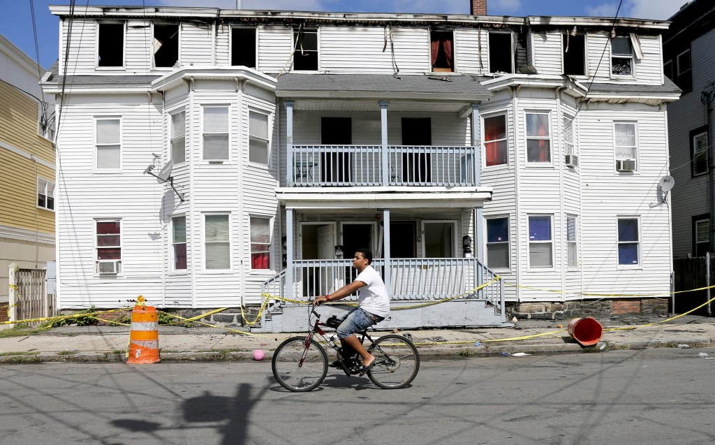 A man on a bicycle rides past a house destroyed by fire on Springfield St in Lawrence, Mass., Friday, Sept. 14, 2018. Multiple houses were damaged Thu