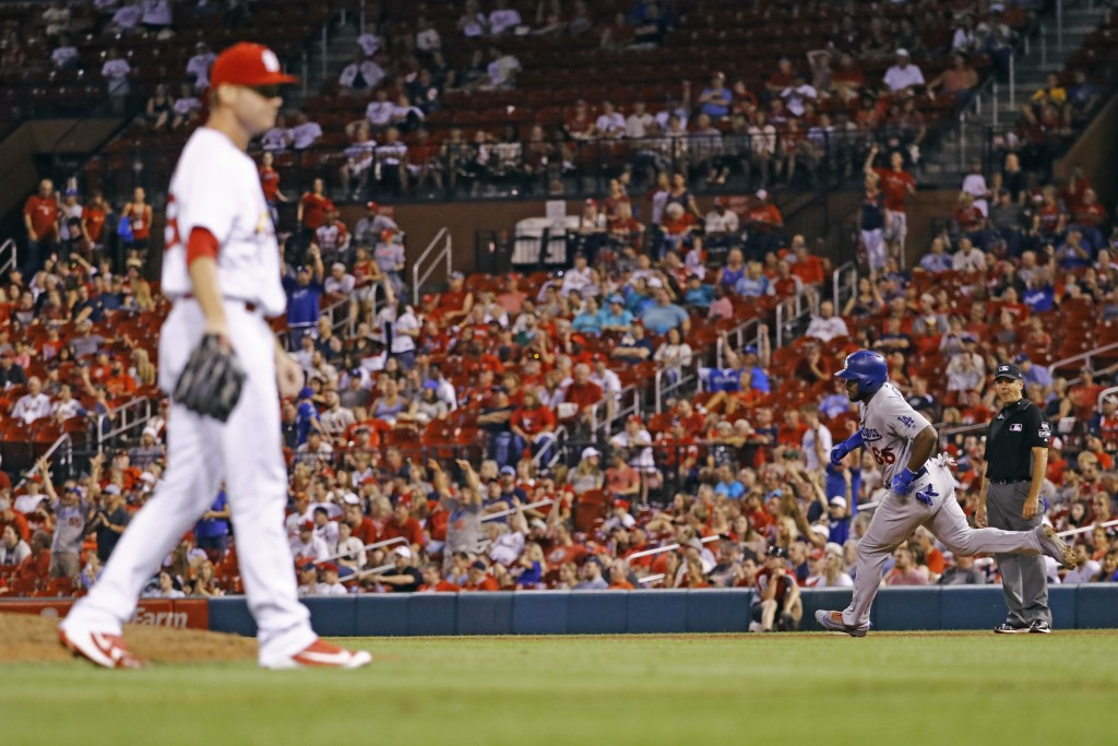 Los Angeles Dodgers' Yasiel Puig, back right, rounds the bases after hitting a home run off of St. Louis Cardinals relief pitcher Tyler Webb, left, du