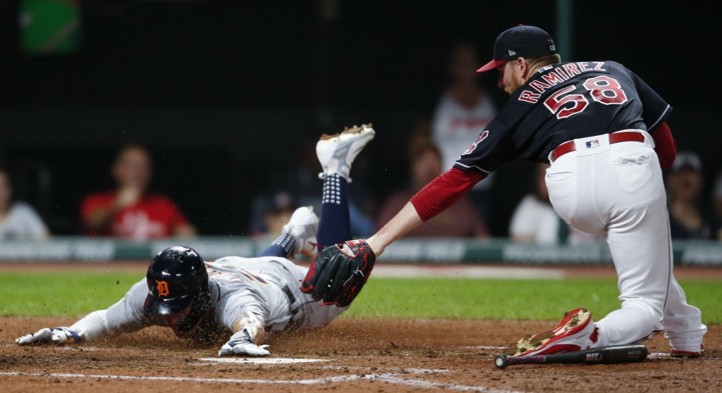 Detroit Tigers' JaCoby Jones, left, scores past Cleveland Indians' Neil Ramirez after a wild pitch by Ramirez during the eighth inning of a baseball g